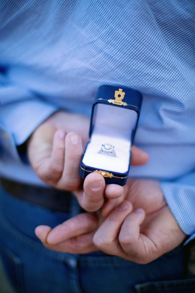 Groom Holding Engagement Ring Box with Fingers Crossed