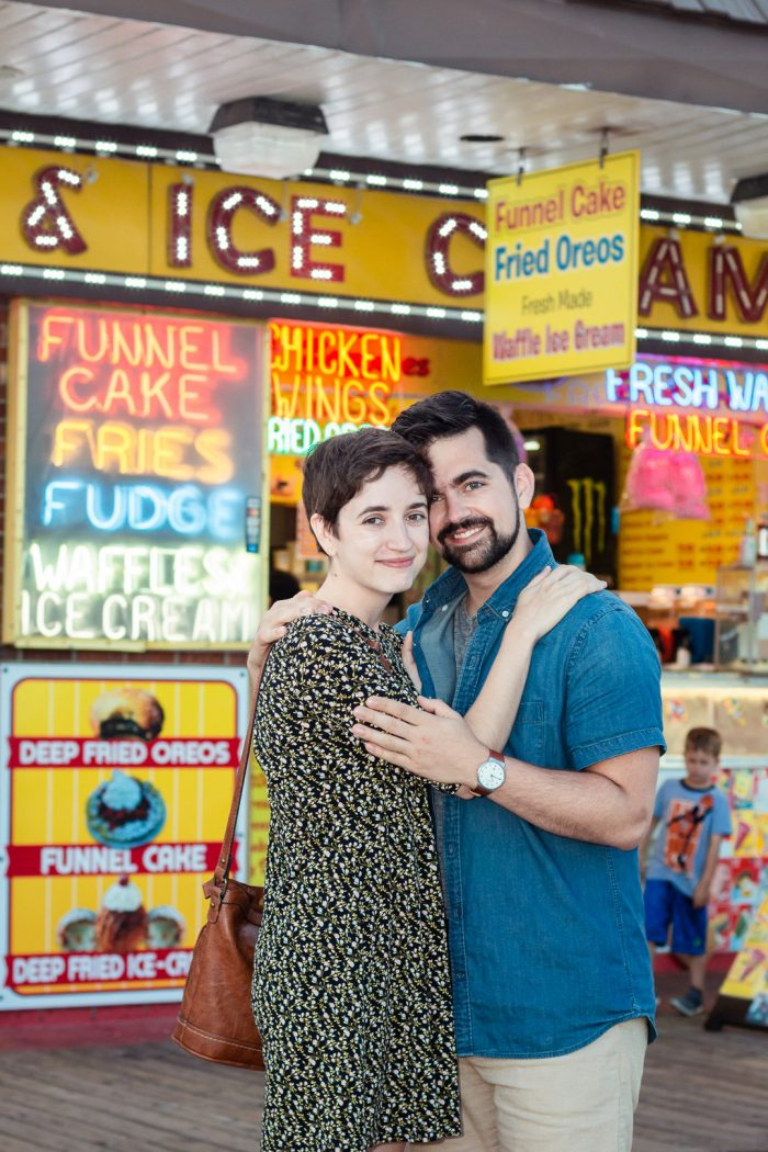 Boardwalk food stand engagement photo with funnel cake, fries, fudge, waffles and ice cream.
