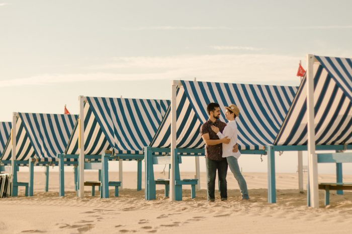 Beach canopy engagement photo at golden hour.