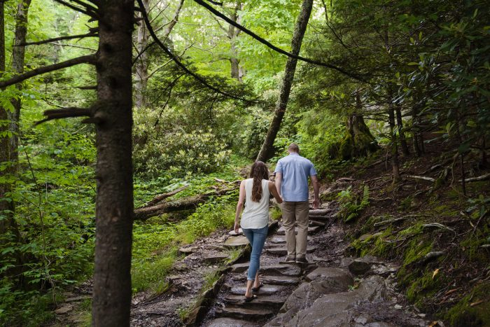 Couple climbs up the stairs of Grandfather Mountain for their engagement shoot.